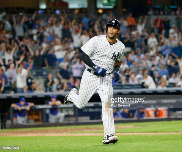 Aaron Hicks of the New York Yankees looks over to his dugout as he runs down the first base line after hitting a home run in an MLB baseball game...