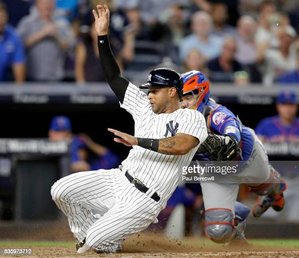 Aaron Hicks of the New York Yankees slides home safely after tagging up on a sacrifice fly as catcher Rene Rivera of the New York Mets covers the...