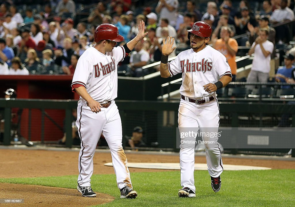 Aaron Hill #2 and Miguel Montero #26 of the Arizona Diamondbacks high-five after scoring first inning runs against the Pittsburgh Pirates during the MLB game at Chase Field on April 9, 2013 in Phoenix, Arizona.