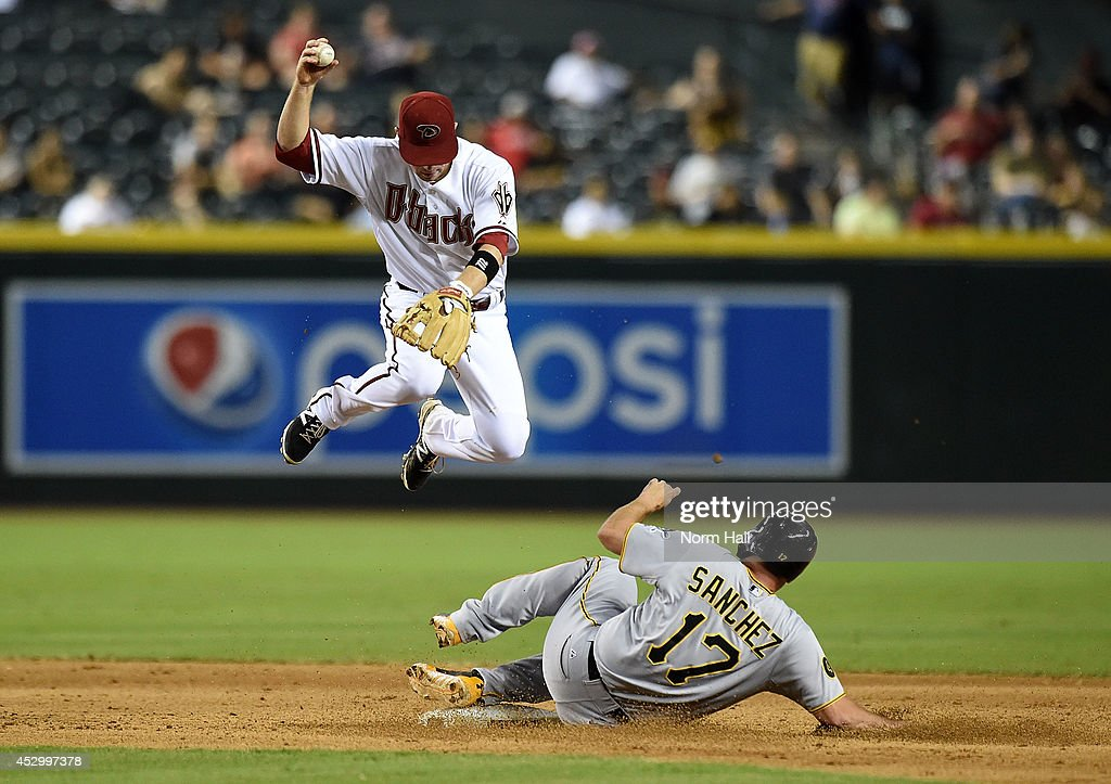 Aaron Hill of the Arizona Diamondbacks attempts to turn a double play while leaping over Gaby Sanchez of the Pittsburgh Pirates at Chase Field on...