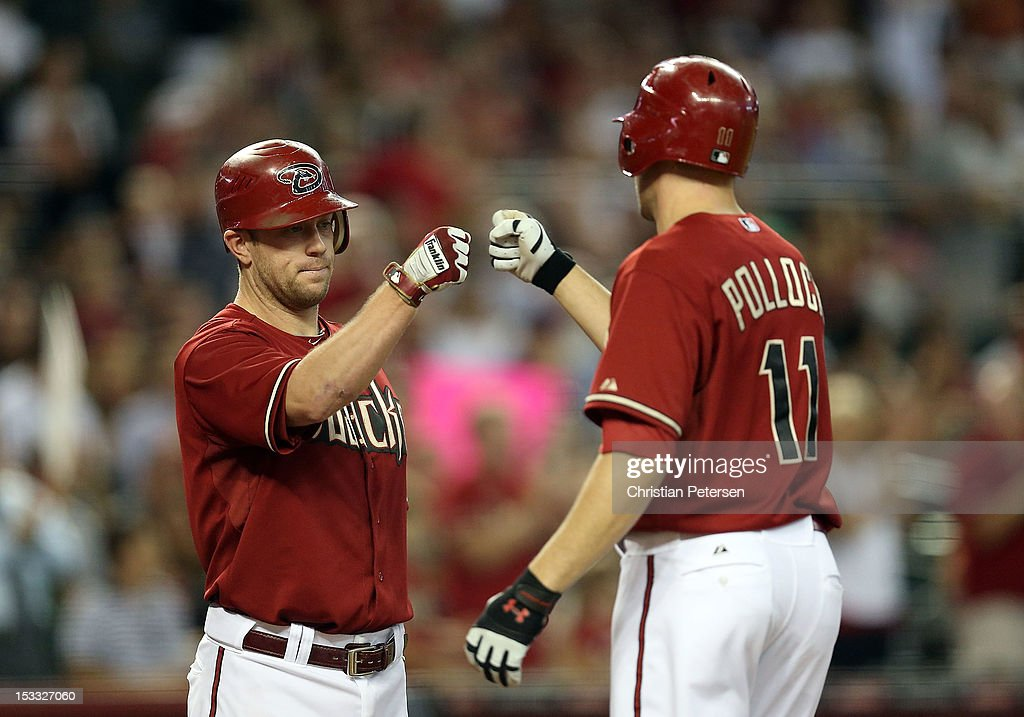 Aaron Hill #2 of the Arizona Diamondbacks congratulates A.J. Pollock #11 after Pollock hit a solo home run against the Colorado Rockies during the third inning of the MLB game at Chase Field on October 3, 2012 in Phoenix, Arizona.