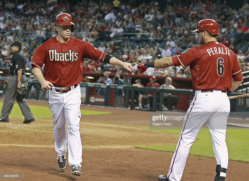 <a gi-track='captionPersonalityLinkClicked' href=/galleries/search?phrase=Aaron+Hill+-+Baseball+Player&family=editorial&specificpeople=239242 ng-click='$event.stopPropagation()'>Aaron Hill</a> #2 of the Arizona Diamondbacks (L) is congratulated by teammate <a gi-track='captionPersonalityLinkClicked' href=/galleries/search?phrase=David+Peralta&family=editorial&specificpeople=9681543 ng-click='$event.stopPropagation()'>David Peralta</a> #6 after scoring a run against the Colorado Rockies during the first inning of a MLB game at Chase Field on August 31, 2014 in Phoenix, Arizona.