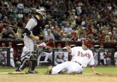 Aaron Hill of the Arizona Diamondbacks is forced out at home plate by catcher Jordan Pacheco of the Colorado Rockies during the sixth inning of the...