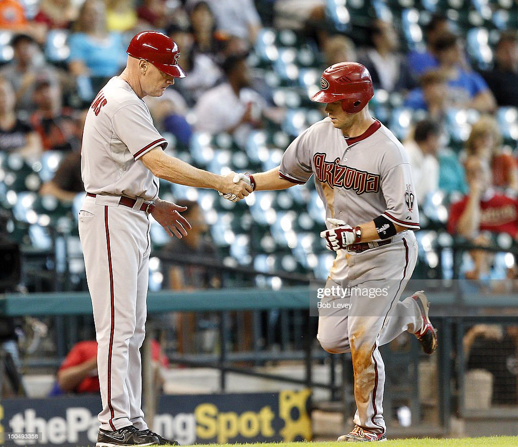 Aaron Hill #2 of the Arizona Diamondbacks receives congratulations by third base coach Matt Williams #9 after hitting a home run in the eighth inning against the Houston Astros at Minute Maid Park on August 19, 2012 in Houston, Texas.
