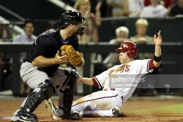 Aaron Hill of the Arizona Diamondbacks safely slides in to score a run past the tag from catcher Chris Iannetta of the Colorado Rockies during the...