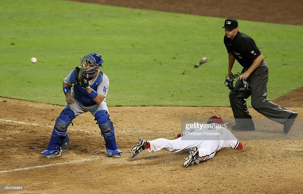 <a gi-track='captionPersonalityLinkClicked' href=/galleries/search?phrase=Aaron+Hill+-+Baseball+Player&family=editorial&specificpeople=239242 ng-click='$event.stopPropagation()'>Aaron Hill</a> #2 of the Arizona Diamondbacks slides in to score a run past catcher A.J. Ellis #17 of the Los Angeles Dodgers during the ninth inning of the MLB game at Chase Field on August 26, 2014 in Phoenix, Arizona. The Dodgers defeated the Diamondbacks 9-5.