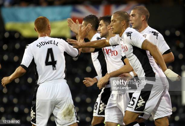 Aaron Hughes of Fulham celebrates scoring the opening goal with teammates Steve Sidwell and Bobby Zamora during the UEFA Europa League PlayOff round...