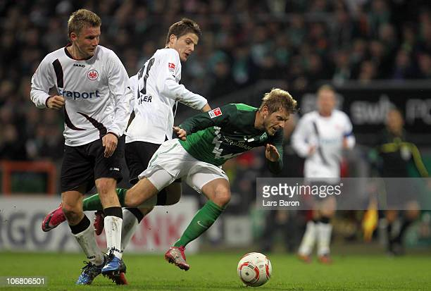 Aaron Hunt of Bremen is challenged by Maik Franz and Pirmin Schwegler of Frankfurt during the Bundesliga match between SV Werder Bremen and Eintracht...