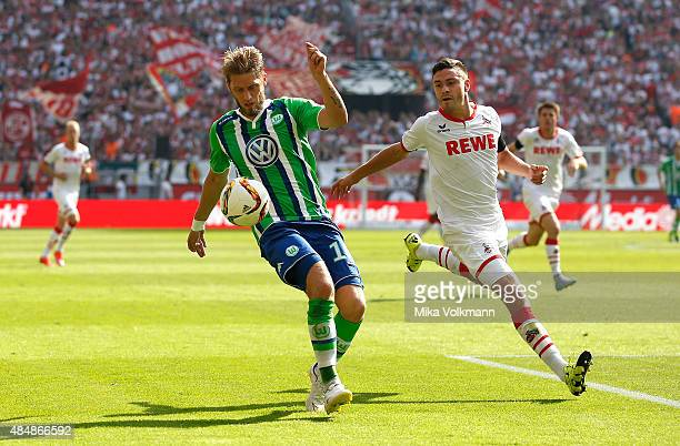 Aaron Hunt of Wolfsburg challenges Jonas Hector of Cologne during the Bundesliga match between 1 FC Koeln and VfL Wolfsburg at RheinEnergieStadion on...