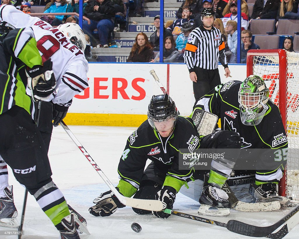 Aaron Irving #24 (L) and Tyler Santos #35 (R) of the Edmonton Oil Kings defend net against Conner Bleackley #9 of the Red Deer Rebels during a WHL game at Rexall Place on March 16, 2014 in Edmonton, Alberta, Canada. The Rebels defeated the Oil Kings 5-0.