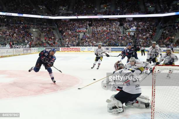 Aaron Johnson of Mannheim takes a shot at the goal against goalkeeper Petri Vehanen of Berlin during the DEL Playoffs quarter finals Game 1 between...