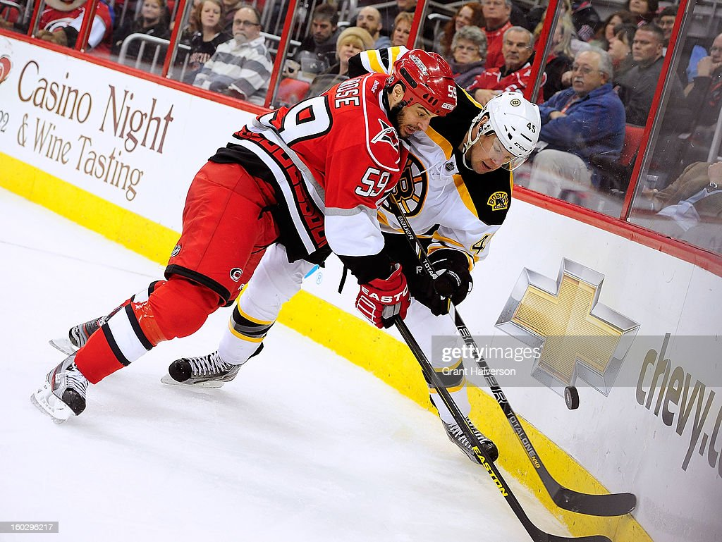 Aaron Johnson #45 of the Boston Bruins battles for a puck in the corner with Chad LaRose #59 of the Carolina Hurricanes during play at PNC Arena on January 28, 2013 in Raleigh, North Carolina.