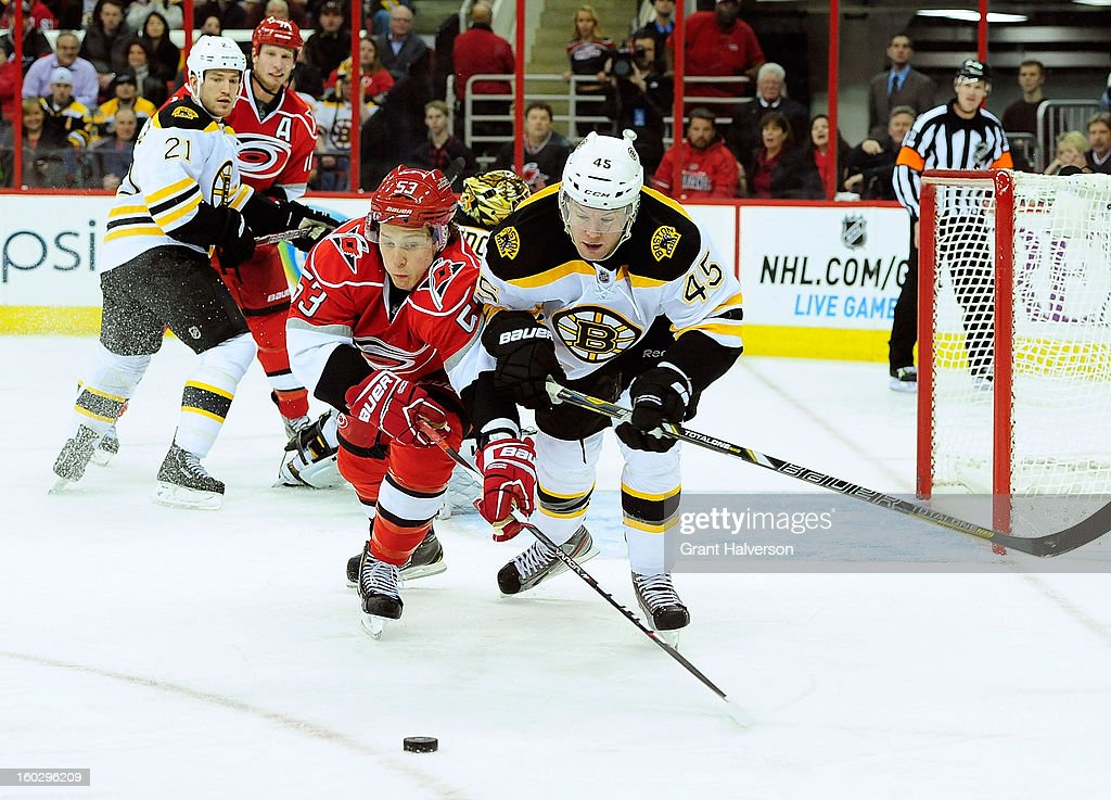 Aaron Johnson #45 of the Boston Bruins battles for the puck with Jeff Skinner #53 of the Carolina Hurricanes during play at PNC Arena on January 28, 2013 in Raleigh, North Carolina.