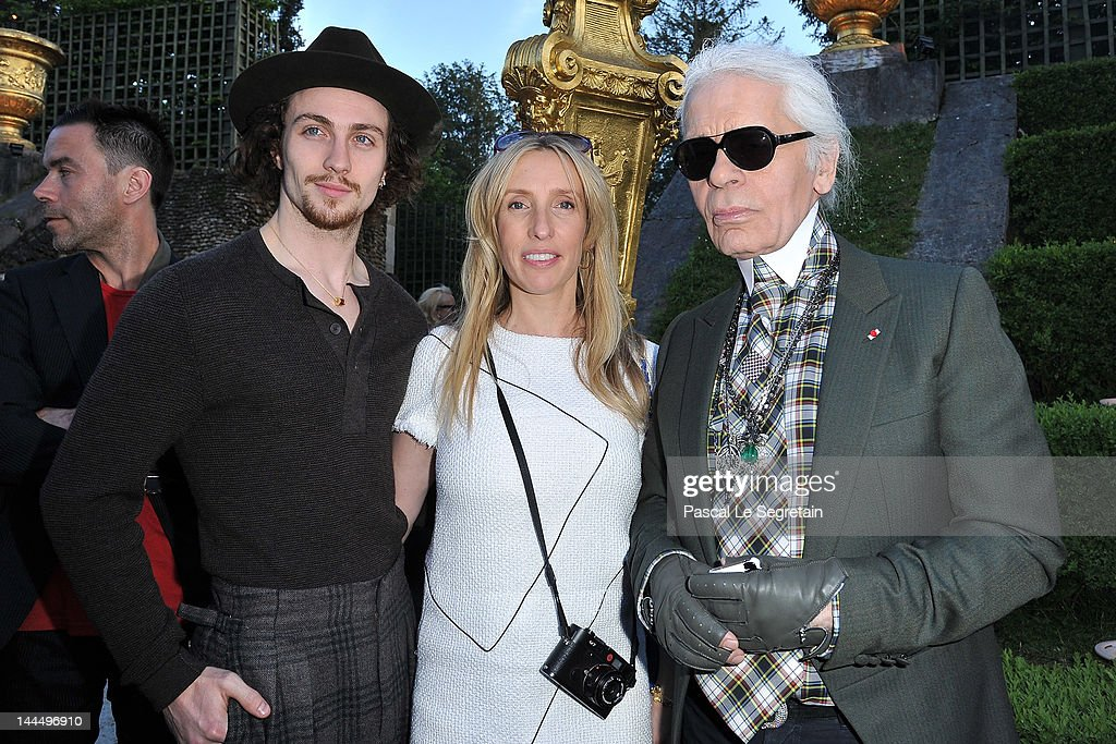 Aaron Johnson, <a gi-track='captionPersonalityLinkClicked' href=/galleries/search?phrase=Sam+Taylor-Wood&family=editorial&specificpeople=206600 ng-click='$event.stopPropagation()'>Sam Taylor-Wood</a> and Karl Lagerfeld pose during the Chanel 2012/13 Cruise Collection at Chateau de Versailles on May 14, 2012 in Versailles, France.