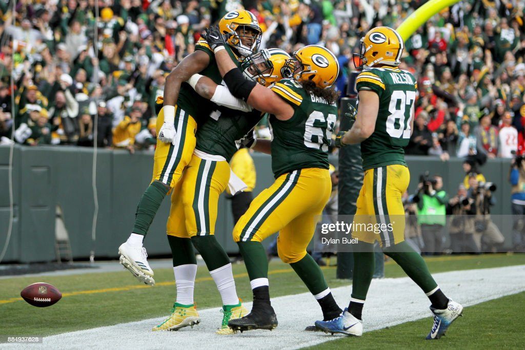 Aaron Jones #33 of the Green Bay Packers celebrates with teammates after scoring a touchdown to beat the Tampa Bay Buccaneers 26-20 in overtime at Lambeau Field on December 3, 2017 in Green Bay, Wisconsin.