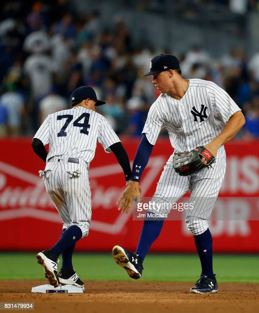 Aaron Judge and Ronald Torreyes of the New York Yankees celebrate after defeating the New York Mets at Yankee Stadium on August 14 2017 in the Bronx...
