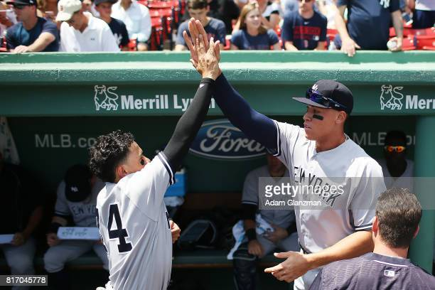 Aaron Judge high fives Ronald Torreyes of the New York Yankees before game one of a doubleheader against the Boston Red Sox at Fenway Park on July 16...