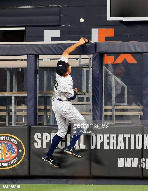 Aaron Judge of the New York Yankees can't come up with a ball hit for a third inning home run by Yoenis Cespedes of the New York Mets at Yankee...
