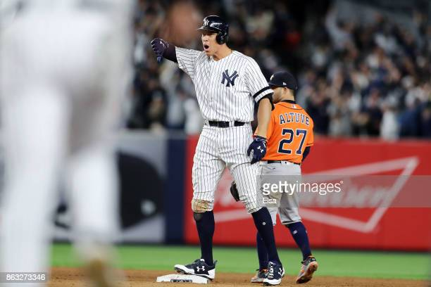 Aaron Judge of the New York Yankees celebrates after hitting a ground rule double in the eight inning as Jose Altuve of the Houston Astros looks on...