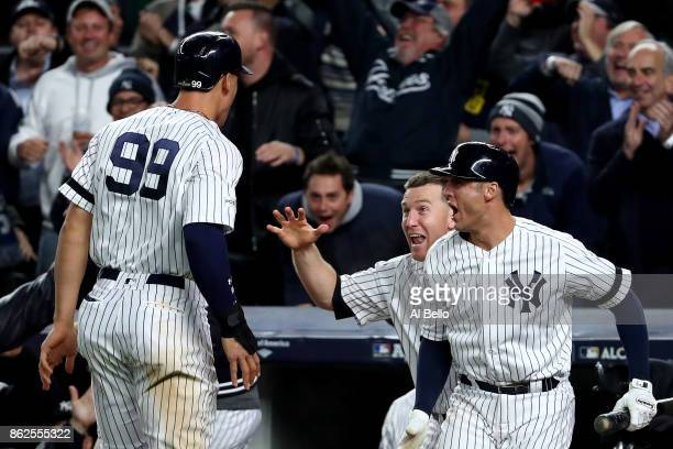 Aaron Judge of the New York Yankees celebrates after scoring on a Gary Sanchez double with Todd Frazier and Greg Bird during the eighth inning...