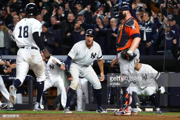 Aaron Judge of the New York Yankees celebrates as he and teammate Didi Gregorius score on a tworun goahead double by Gary Sanchez during the eighth...