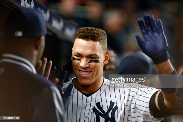 Aaron Judge of the New York Yankees celebrates his fifthinning tworun home run against the Chicago White Sox with his teammates in the dugout at...