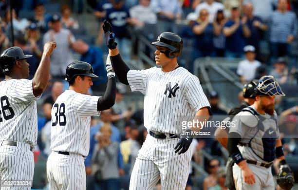 Aaron Judge of the New York Yankees celebrates his seventh inning two run home run against the Tampa Bay Rays with teammates Chris Carter and Kyle...