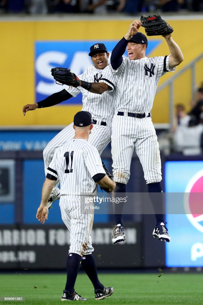 Aaron Judge #99 of the New York Yankees celebrates with teammates Aaron Hicks #31 and Brett Gardner #11 after defeating the Cleveland Indians in Game Four of the American League Divisional Series at Yankee Stadium on October 9, 2017 in the Bronx borough of New York City. The New York Yankees defeated the Cleveland Indians with a score of 7 to 3.