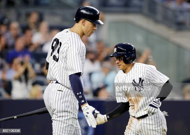Aaron Judge of the New York Yankees congratulates teamamte Ronald Torreyes after he scored in the third inning against the New York Mets during...
