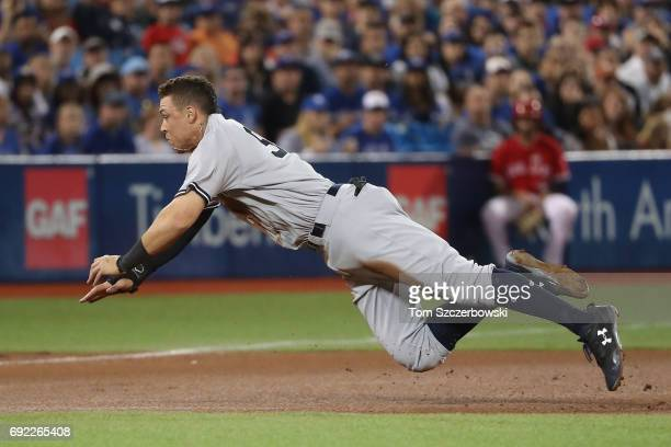 Aaron Judge of the New York Yankees dives safely into third base as he advances from first base on a throwing error in the fourth inning during MLB...