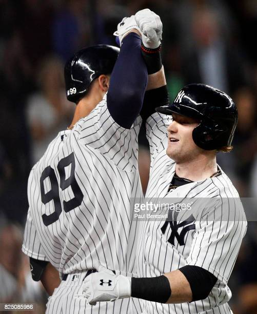 Aaron Judge of the New York Yankees greets teammate Clint Frazier after Frazier crossed the plate with his home run in the 5th inning of an MLB...
