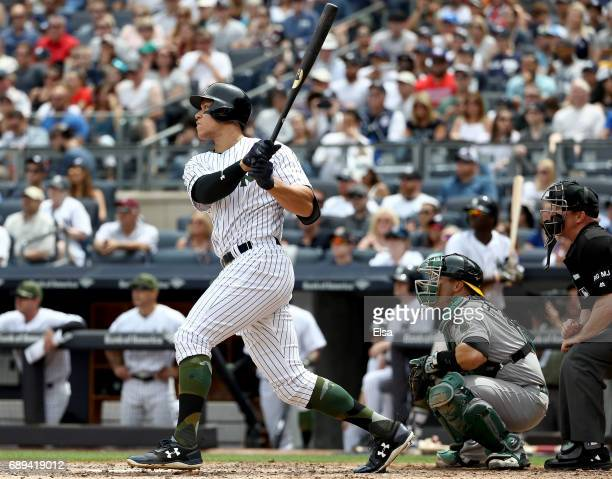 Aaron Judge of the New York Yankees hits a grand slam in the third inning as Josh Phegley of the Oakland Athletics defends on May 28 2017 at Yankee...