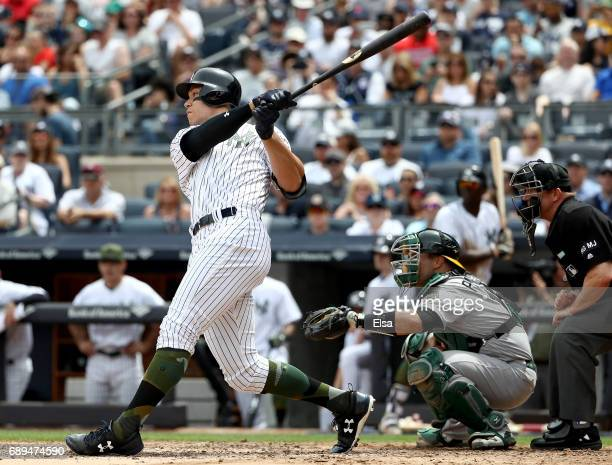 Aaron Judge of the New York Yankees hits his first career grand slam in the third inning as Josh Phegley of the Oakland Athletics defends on May 28...
