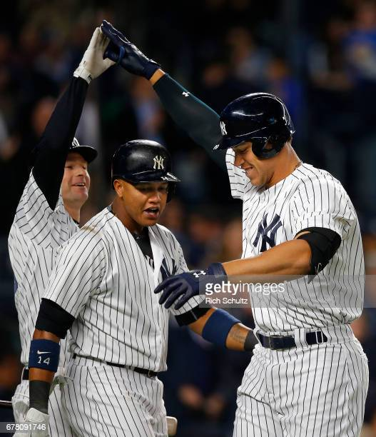 Aaron Judge of the New York Yankees is congratulated by Chase Headley and Starlin Castro after he hit a tworun home run in the third inning against...