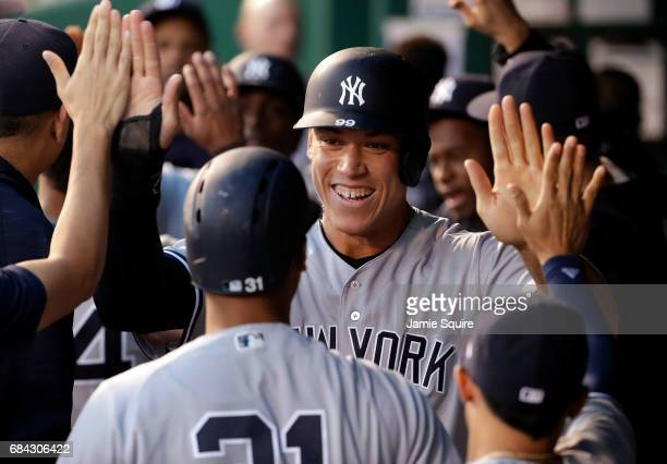 Aaron Judge of the New York Yankees is congratulated by teammates in the dugout after scoring during the 4th inning of the game against the Kansas...
