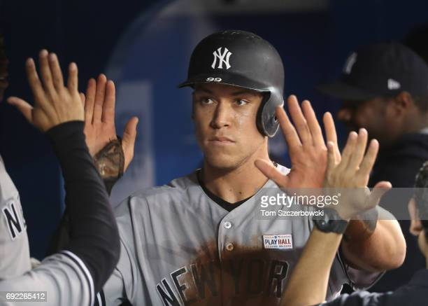 Aaron Judge of the New York Yankees is congratulated by teammates in the dugout after scoring a run in the fourth inning during MLB game action...