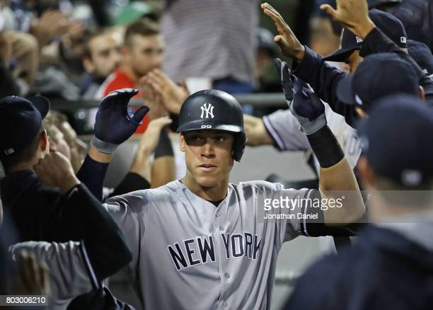 Aaron Judge of the New York Yankees is congratulated by teammates in the dugout after hitting a two run home run in the 6th inning against the...