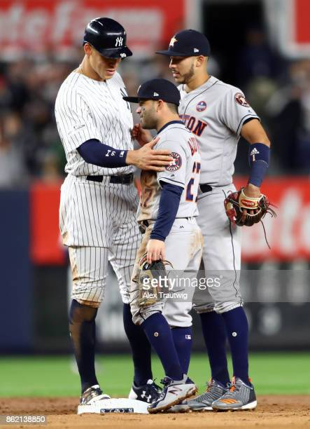 Aaron Judge of the New York Yankees jokes with Jose Altuve and Carlos Correa of the Houston Astros during Game 3 of the American League Championship...
