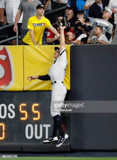 Aaron Judge of the New York Yankees leaps and reaches above the wall in right field to rob Francisco Lindor of a home run in the 6th inning of game 3...