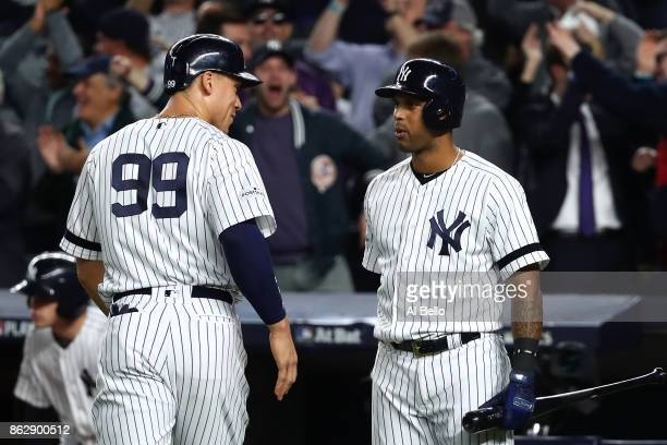 Aaron Judge of the New York Yankees reacts with Aaron Hicks after scoring on a single by Didi Gregorius during the fifth inning against the Houston...