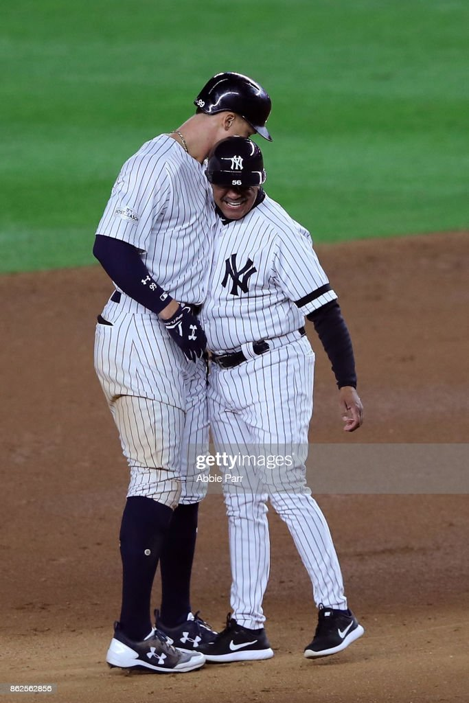 Aaron Judge #99 of the New York Yankees reacts with first base coach Tony Pena #56 after hitting a double during the eighth inning against the Houston Astros in Game Four of the American League Championship Series at Yankee Stadium on October 17, 2017 in the Bronx borough of New York City.