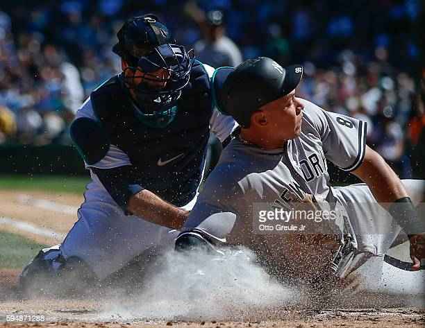 Aaron Judge of the New York Yankees scores against catcher Chris Iannetta of the Seattle Mariners in the second inning at Safeco Field on August 24...