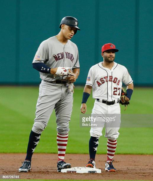 Aaron Judge of the New York Yankees talks with Jose Altuve of the Houston Astros after hitting a double in the first inning at Minute Maid Park on...