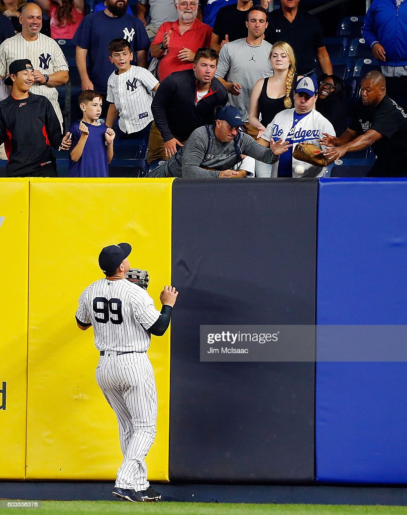Aaron Judge #99 of the New York Yankees watches fans reach for a ball hit for a home run in the ninth inning by Justin Turner of the Los Angeles Dodgers at Yankee Stadium on September 12, 2016 in the Bronx borough of New York City.