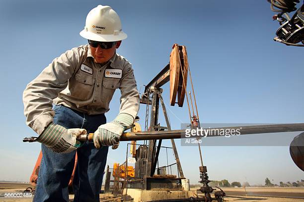 Aaron Kent a wireline operator for Canary LLC works on a slick line at an oil rig pump jack site in the oil fields near Bakersfield on March 13 2013...