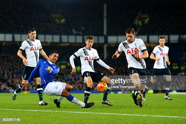 Aaron Lennon of Everton crosses the ball under pressure from the Tottenham defence during the Barclays Premier League match between Everton and...
