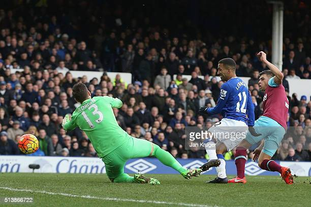 Aaron Lennon of Everton scores his team's second goal past Adrian of West Ham United during the Barclays Premier League match between Everton and...