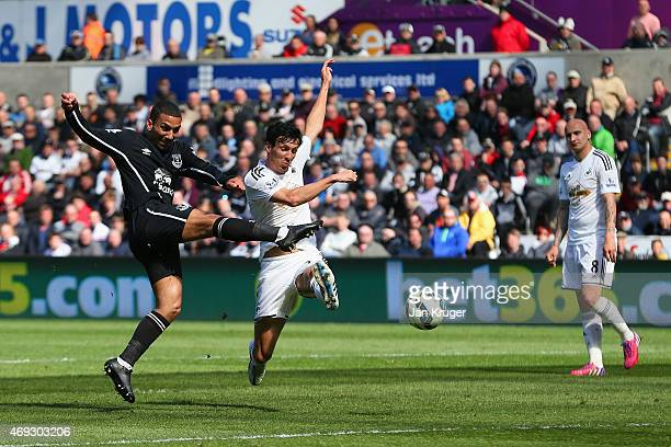 Aaron Lennon of Everton scores the first goal past Jack Cork of Swansea City during the Barclays Premier League match between Swansea City and...