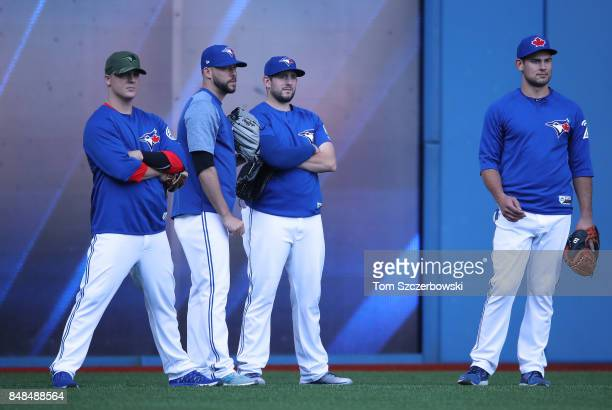Aaron Loup of the Toronto Blue Jays and Ryan Tepera and Dominic Leone and Luke Maile look on from the outfield as they warm up during batting...