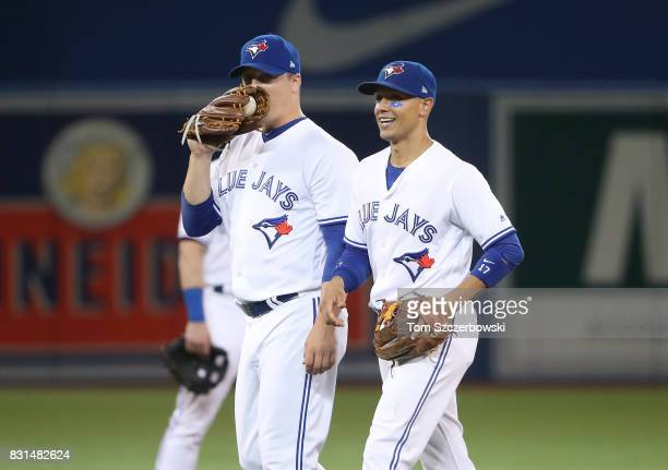 Aaron Loup of the Toronto Blue Jays shares a laugh with Ryan Goins after a double play at second base was reversed following a video replay review in...